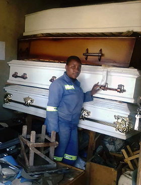 Fifteen-year-old Vanessa Chingwende stands beside finished coffins ready for sale in her workshop room near Marange, Zimbabwe. Photo by Chenayi Kumuterera, UM News.