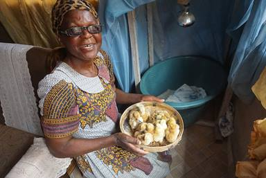 Nyengeterai Mafongoya holds a basket of 20-day-old chicks in Masvingo, Zimbabwe. She started with 20 chicks as part of a United Methodist Women poultry project in February and grown her brood to 100 birds.  Photo by Kudzai Chingwe, UM News.