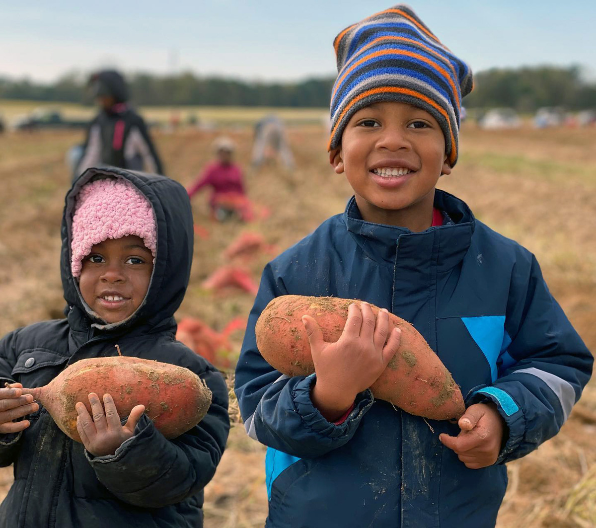 Olivia (left) and Judah Brown hold sweet potatoes at First Fruits Farm in Louisburg, N.C. Owned by their parents Jason and Tay Brown, the farm supplies produce to Society of St. Andrew, which is helping get food to needy citizens. Photo courtesy of the Browns.