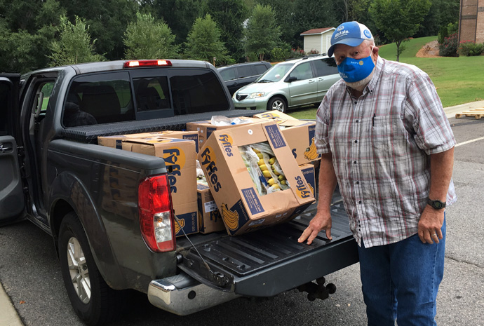B.J. Copeland loads boxes of bananas into the back of his truck. Copeland is one of a group of volunteers who help haul produce to centers that are able to get the food to churches and food banks. Photo courtesy of B.J. Copeland.