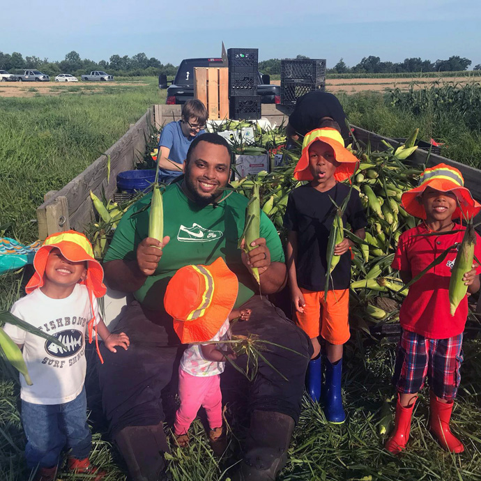 Former NFL center Jason Brown sits on the back of a flatbed truck full of corn with his children (from left) Judah, Jason, Olivia, Noah and Tre. First Fruits Farm, Browns' farm in Louisburg, N.C., donates almost all of its harvest to the Society of St. Andrew. Photo courtesy of the Browns.