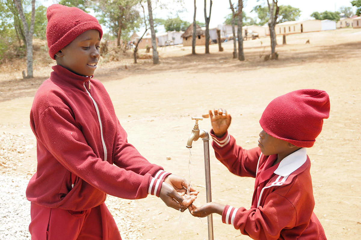Students Munashe Chidewu (left) and Nyasha Homba wash their hands at a faucet served by a solar-powered well pump at the United Methodist Hanwa Mission in Macheke, Zimbabwe. Photo by Kudzai Chingwe, UM News.