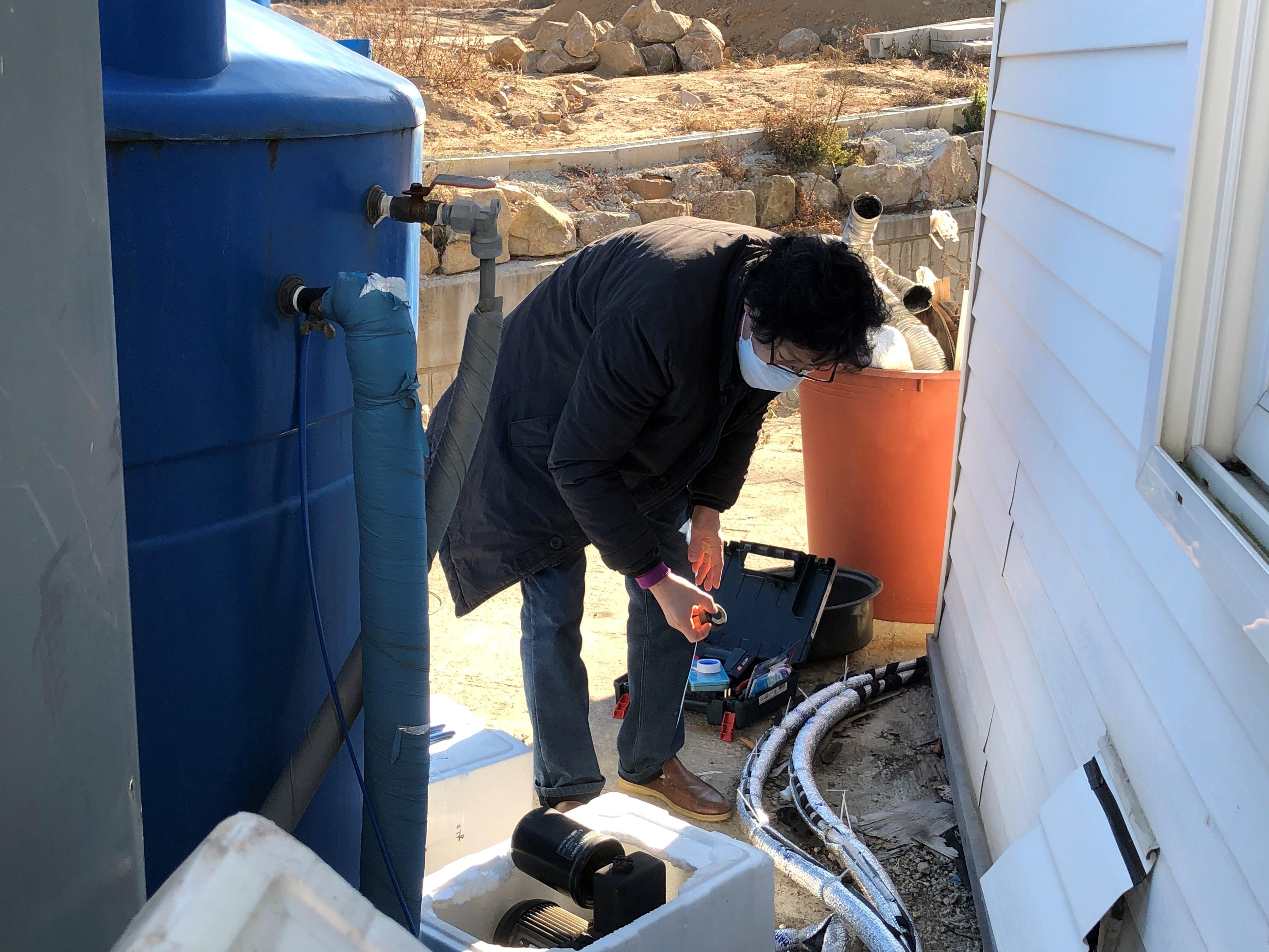 웨슬리사회성화실천본부의 안완구 목사가 추운 날씨에도 불구하고 선교사들이 격리하고 있는 무의도 수양관의 펌프를 수리하고 있다. 사진, 김응선 목사, 연합감리교뉴스.