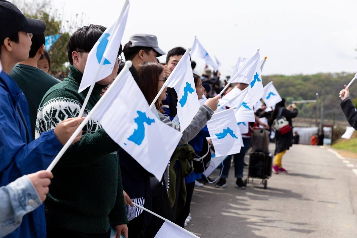 남한과 북한 사이의 500km 길이의 비무장 지대를 따라 손에 손을 잇고 <평화인간띠운동>에 참가한 한국인들. 사진 제공, 박종천 목사, 한국기독교교회협의회(NCCK)