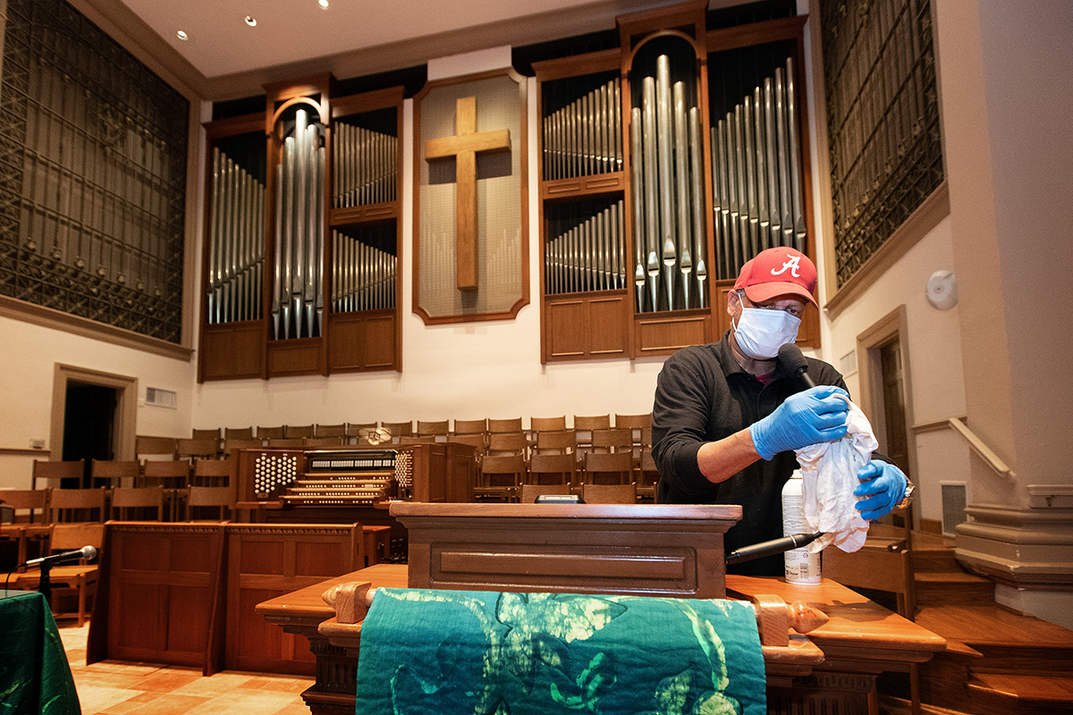 "Custodian James Jimmerson disinfects a microphone to prevent any possible spread of the coronavirus at Belmont United Methodist Church in Nashville, Tenn., on Sunday, May 10, following online worship, which is recorded in the sanctuary. As churches considered returning to in-person worship, cleaning measures are one of many factors leaders considered. ""I believe my job, my part in this, is to make sure people are safe in here,"" Jimmerson said. File photo by Mike DuBose, UM News."