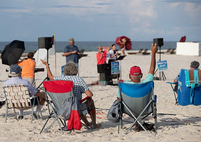 Worshippers raise their arms in praise during the Galilean Beach Service, a ministry of Foley (Ala.) United Methodist Church at Gulf State Park in Gulf Shores, Ala., on Sunday, Aug. 9. The 7:30 a.m. service was over before most other beachgoers arrived. File photo by Mike DuBose, UM News.