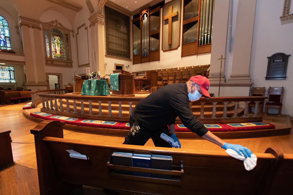 Le gardien James Jimmerson désinfecte les bancs pour prévenir toute propagation possible du coronavirus à l'église Méthodiste Unie Belmont de Nashville, Tennessee, le dimanche 10 mai 2020, à la suite d'un culte en ligne, qui est enregistré dans le sanctuaire. Alors que les églises envisagent de revenir au culte en présentiel, les mesures de nettoyage sont l'un des nombreux facteurs dont les responsables devront tenir compte. « Je crois que mon travail, mon rôle dans tout cela, est de m'assurer que les gens sont en sécurité ici, » a déclaré M. Jimmerson. Photo de Mike DuBose, UM News.