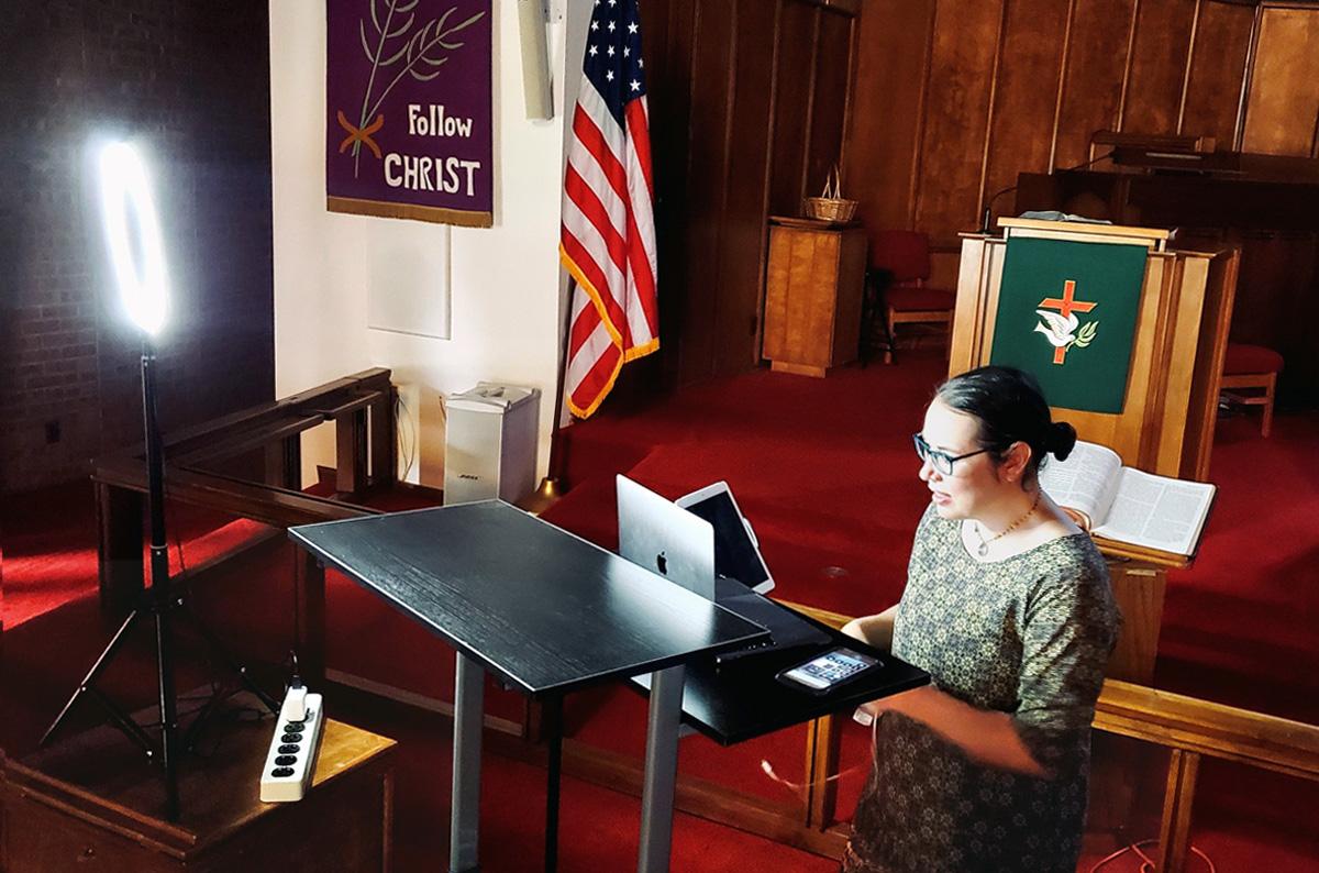 La Revda. Amy Wilson Feltz, pastora de la Iglesia Metodista Unida de St. Paul en El Paso, estado de Tejas, instala equipos informáticos para transmitir un sermón en vivo en el santuario de la iglesia en septiembre. Aunque el púlpito, que es visible en cámara, tiene el color litúrgico apropiado, el estandarte en la pared era de Cuaresma, cuando la iglesia tuvo que suspender el culto en persona. Foto cortesía de la Revda. Amy Wilson Feltz.