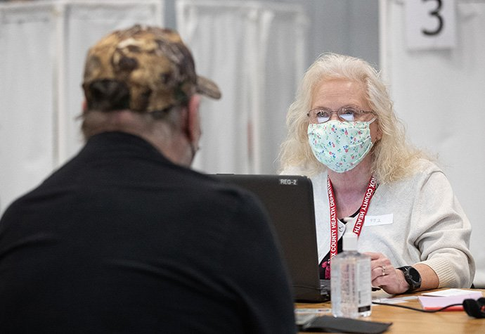 Volunteer Dorothy Fish takes information from a patient who will receive a COVID-19 vaccination at Community United Methodist Church in Vincennes, Ind., where Fish is a member. Photo by Mike DuBose, UM News.