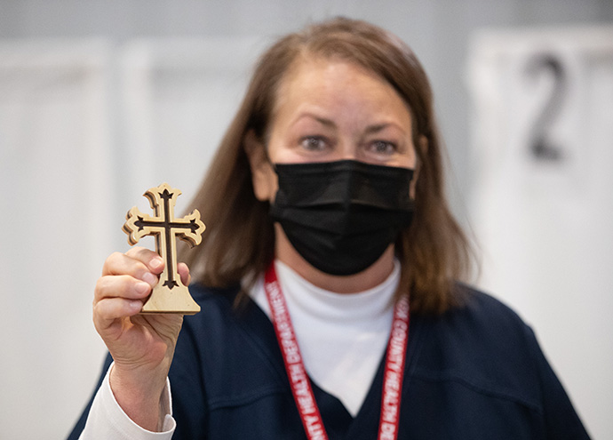 Volunteer Jackie Smith, RN, displays a wooden cross given to her by a grateful patient who had received a COVID-19 vaccination from her at Community United Methodist Church in Vincennes, Ind. Photo by Mike DuBose, UM News.