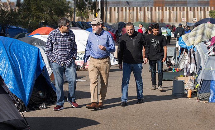 Bishop Felipe Ruiz Aguilar (left) of the Methodist Church of Mexico, the Revs. Jack Amick (center) of the United Methodist Committee on Relief and Edgar Avitia Legarda of the United Methodist Board of Global Ministries survey a makeshift camp for migrants outside the Benito Juarez sports complex in Tijuana, Mexico, in 2018. Global Ministries, the denomination's largest agency, has been cutting its operating budget significantly over the past few years. File photo by Mike DuBose, UM News.