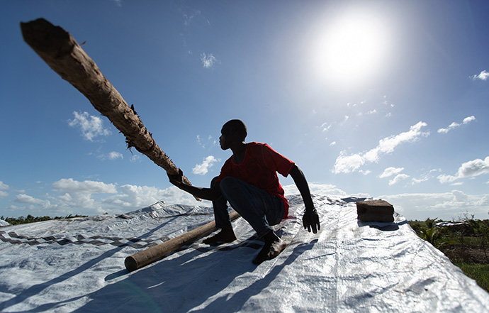 Jorge João Novo lifts a wooden pole into place to help secure an emergency tarp over his home after the roof was peeled off by Cyclone Idai in Búzi, Mozambique, in 2019. The most recent storm, Cyclone Eloise, hit many areas that were just beginning to recover from previous storms. File photo by Mike DuBose, UM News.