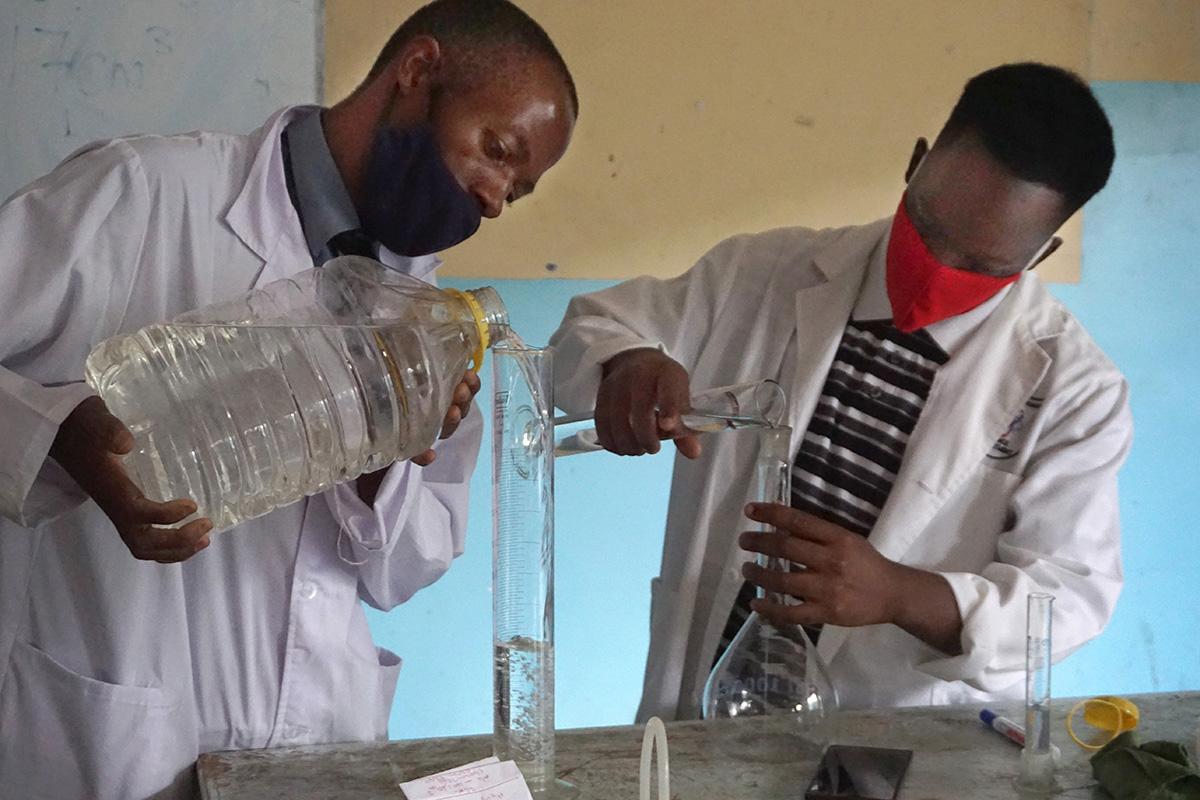 Innocent Mushayavanhu (à gauche) et Tariraishe Mubazangi préparent un désinfectant pour les mains au lycée Murewa de l'Église Méthodiste Unie au Zimbabwe. « Nous avons réussi à préparer des désinfectants et des masques pour cette école de 1 250 lèves, 30 travailleurs et 55 enseignants, » a déclaré Sydney Mapisaunga, directeur de l'école. Photo de Kudzai Chingwe, UM News.