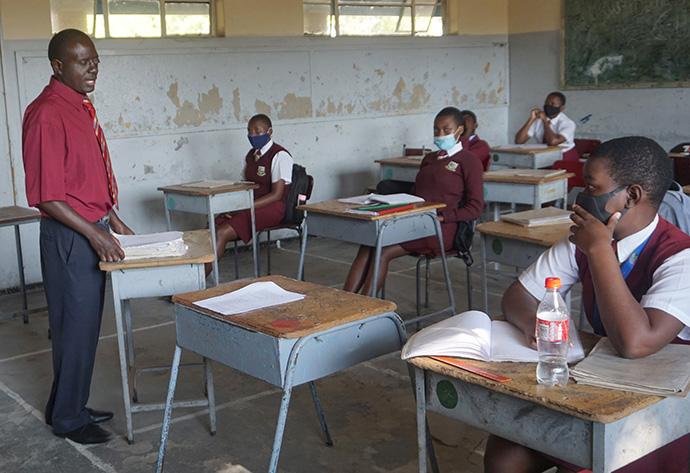 Luckmore Mondiwa enseigne l'histoire à des élèves portant des masques au lycée de Murewa de l'Église Méthodiste Unie, au Zimbabwe. Les élèves et les enseignants du Zimbabwe ont du mal à apprendre et à enseigner puisque les restrictions de confinement liées à la COVID-19 se poursuivent. Photo de Kudzai Chingwe, UM News.