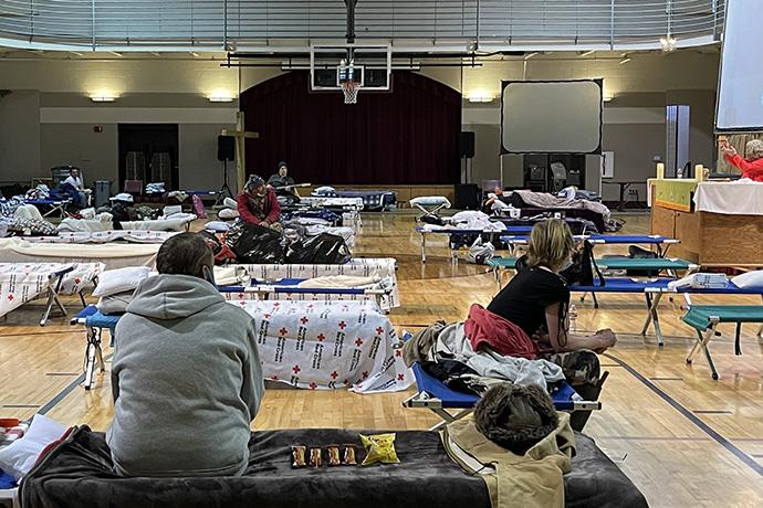 A las personas que buscan refugio de la nieve y el frío se les ofrece la Comunión en el gimnasio de la Primera Iglesia Metodista Unida en Hot Springs, Arkansas. La iglesia está operando el refugio en cooperación con la Cruz Roja local. Foto de Cindy English.