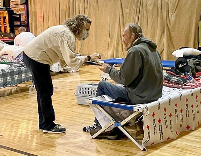 Haley Villines offers Holy Communion to a guest in the church gymnasium serving as a warming shelter at First United Methodist Church in Hot Springs, Ark. Photo by Cindy English.