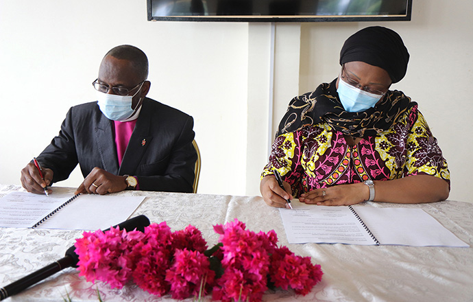 Bishop Benjamin Boni (left) and Lydie Flore Magba, Central African Republic ambassador to Côte d'Ivoire, initial the framework for cooperation in education between The United Methodist Church in Côte d'Ivoire and the Central African Republic in October, 2020. The collaboration aims to revitalize the Central African education system, which has been disorganized by years of successive socio-political and economic crises. File photo by Isaac Broune, UM News.