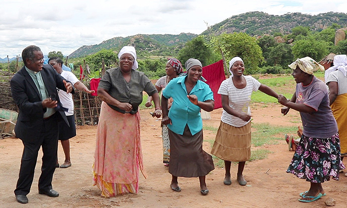 The Rev. Jairos Mafondokoto (left) joins women in Bikita, Zimbabwe, in celebrating the dedication of new homes built with funds from the Baltimore-Washington Conference of The United Methodist Church for survivors of Cyclone Idai. Mafondokoto is superintendent of the Masvingo District of The United Methodist Church in Zimbabwe. Photo by Priscilla Muzerengwa, UM News.