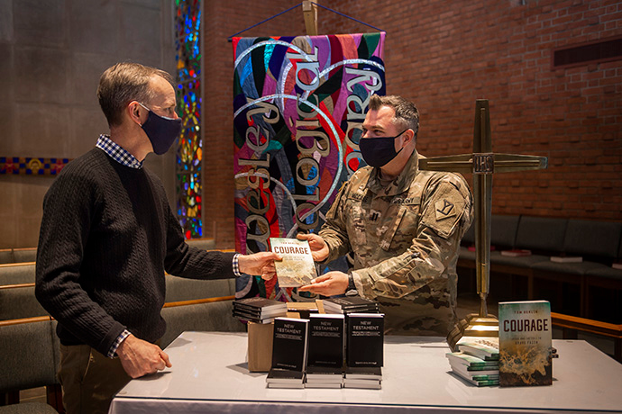 """The Rev. Tom Berlin (left) presents a copy of his book, """"Courage,"""" to Massachusetts National Guard Chaplain Chad McCabe in the chapel at Wesley Theological Seminary in Washington. McCabe, whose unit was assigned to help provide security at the U.S. Capitol after the January riot, contacted Wesley Seminary asking for Bibles, novels and board games for troops stationed there. Photo by Lisa Helfert for Wesley Theological Seminary. Copyright 2021. All rights reserved. Used with permission."""