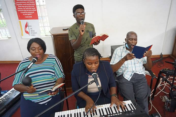 Gospel musicians record a song for an online worship service at Chisipiti United Methodist Church in Harare, Zimbabwe. United Methodists across the country are using music to provide strength and comfort during the pandemic. Seated, from left, are: Patricia Mapani, Christine Anesu Hove and Ricky Mapani. At rear is Ali White. Photo by Kudzai Chingwe, UM News.