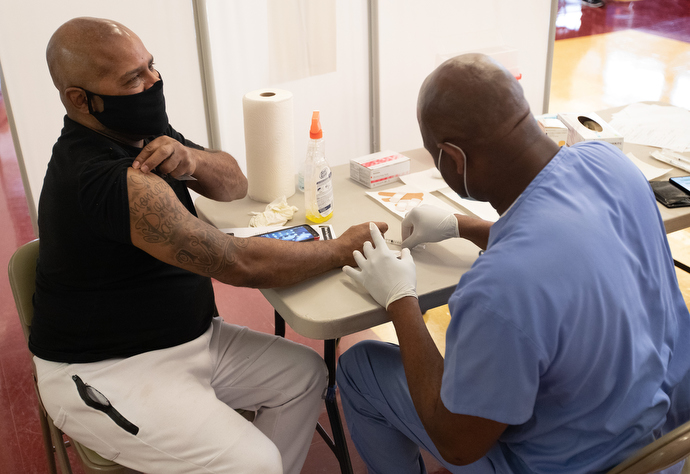 Vincent Richardson rolls up his sleeve to receive a COVID-19 vaccination from Dr. Olayinka Otukpe at Meharry Medical College in Nashville, Tenn. Photo by Mike DuBose, UM News.