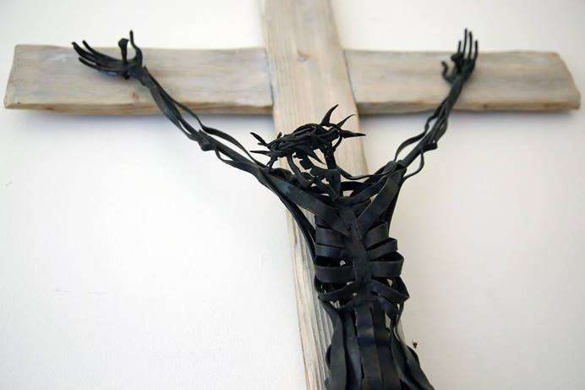 Un crucifijo de metal abstracto cuelga de la pared fuera de la capilla en Sarum College en Salisbury, Inglaterra. Foto de Kathleen Barry, UMCOM.