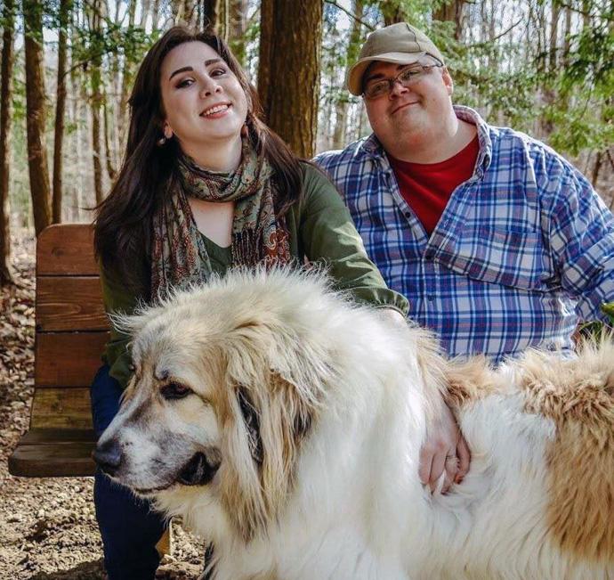 """El Rev. Derek Kubilus se relaja con su esposa Maggie y su perro Beowulf. Kubilus apareció en """"60 Minutos"""" por haber lanzado un podcast sobre el movimiento de conspiración QAnon. Foto de Reanna Lovsey."""