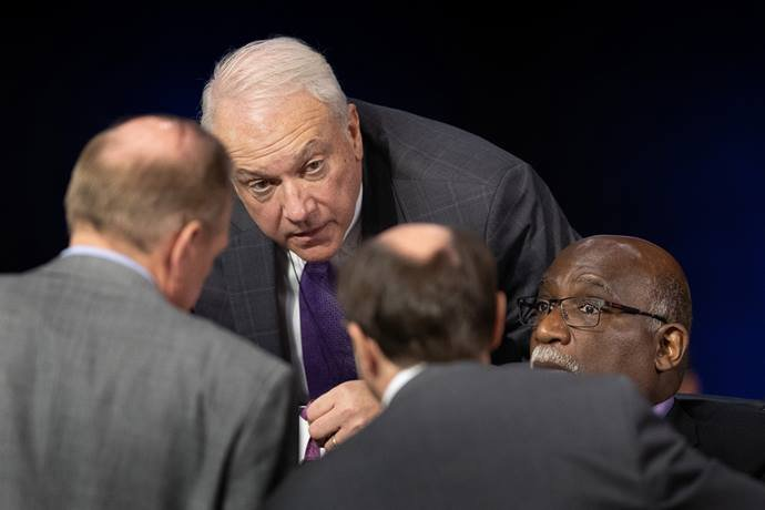 Bishops Thomas J. Bickerton (center) and Gregory V. Palmer (right) confer with colleagues on legislative procedures during the 2019 United Methodist General Conference in St. Louis. Bickerton is the Council of Bishops representative on the Commission on the General Conference. The commission — meeting behind closed doors — reviewed an investigation that found evidence of four ineligible people casting votes using the credentials of delegates who were not present. File photo by Mike DuBose, UM News.