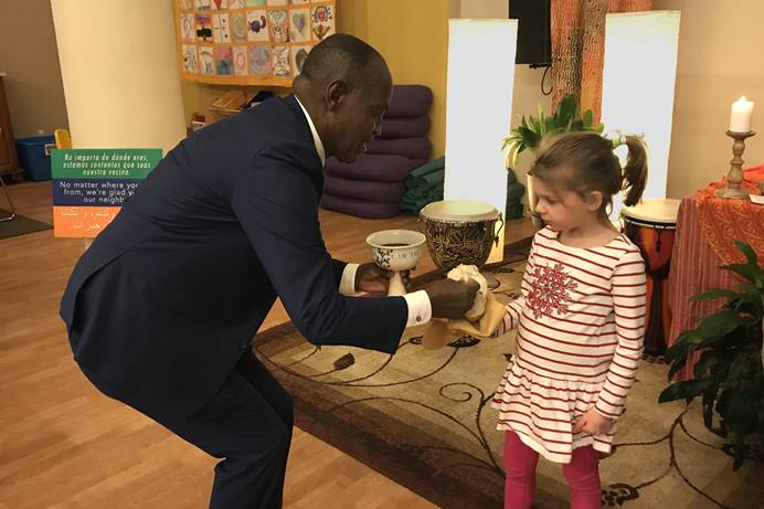 The Rev. Nathan Ndayiziga, a Methodist pastor from Burundi, gives communion to Emilia Lovejoy during a 2019 service at HopeGateWay Church in Portland, Maine. The church is among multiple congregations in the process of disaffiliating from The United Methodist Church. HopeGateWay is doing so in solidarity with LGBTQ members. Photo courtesy of the Rev. Sara Ewing-Merrill.