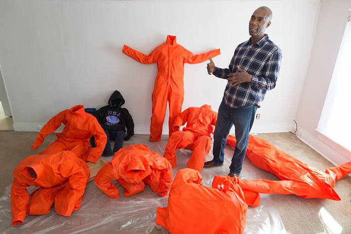 Ndume Olatushani describes his installation artwork featuring human figures in prison-style jumpsuits and hoodies at his home in Nashville, Tenn., in 2017. The work was part of a Stations of the Cross exhibition held in Washington, D.C. Olatushani was freed after serving 27 years in prison, 20 of them on death row. A series of webinars April 26-30 will offer advice to church members on how to support former prison inmates and help them find gainful employment. File photo by Mike DuBose, UM News.