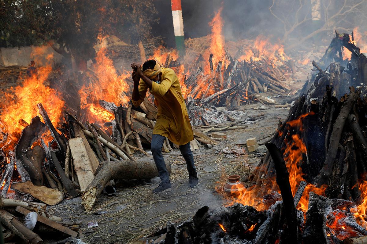한 남자가 인도 뉴델리의 대형 화장터에서 코로나19로 사망한 사람들을 화장하기 위해 움막처럼 쌓아 놓은 불타는 화장용 나무 사이를 뛰어 지나가고 있다. 연합감리교회는 인도의 코로나바이러스 확산으로 인한 위기 상황을 돕기 위한 기금을 모으고 있다. 사진 제공, 아드난 아비디, 로이터통신.