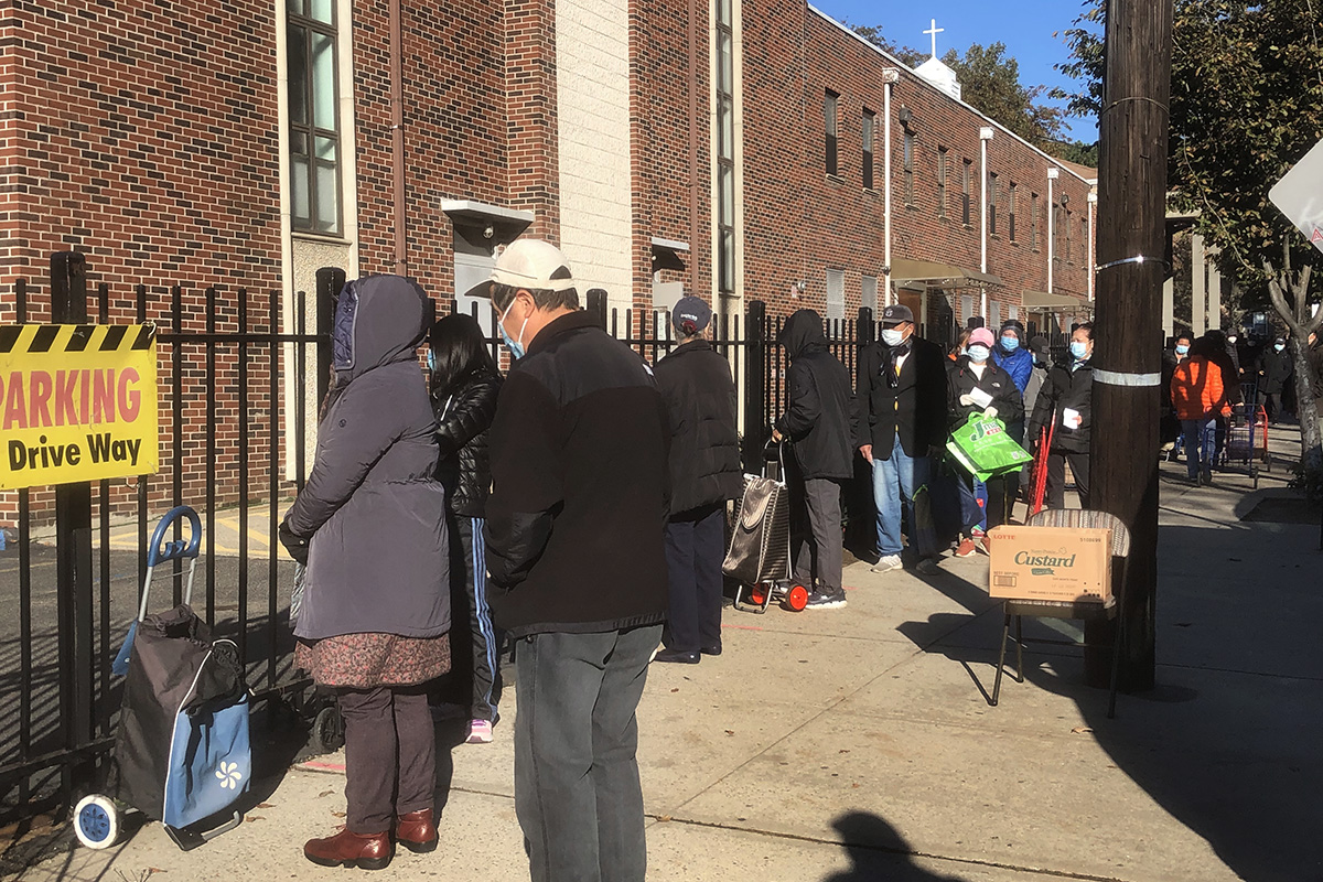 Neighborhood residents wait to receive food during a distribution at First United Methodist Church in Flushing, N.Y. Photo by the Rev. Thomas Kim, UM News.