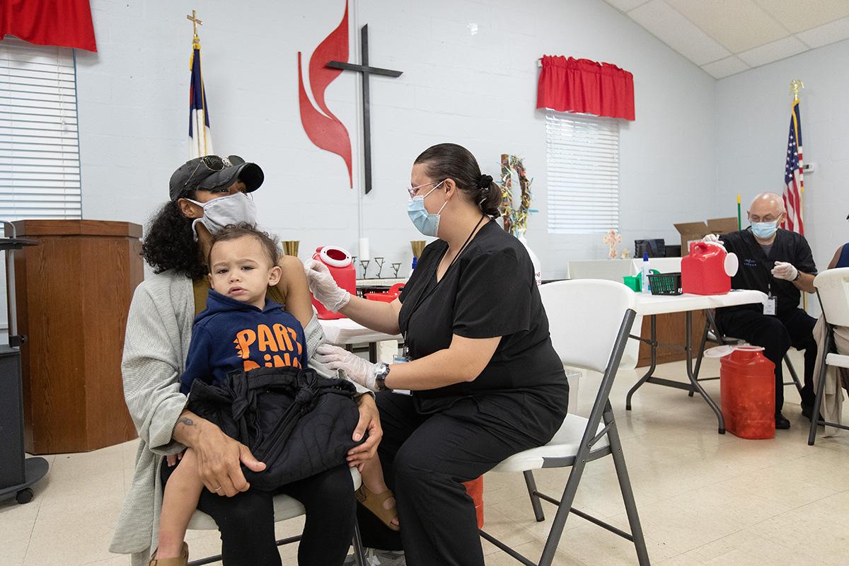 Camisha Henson segura seu filho Welles no colo enquanto recebe a vacinação COVID-19 de Tabitha England, RN, durante uma clínica na Igreja Metodista Unida de St. Mark's em Charlotte, Carolina do Norte.