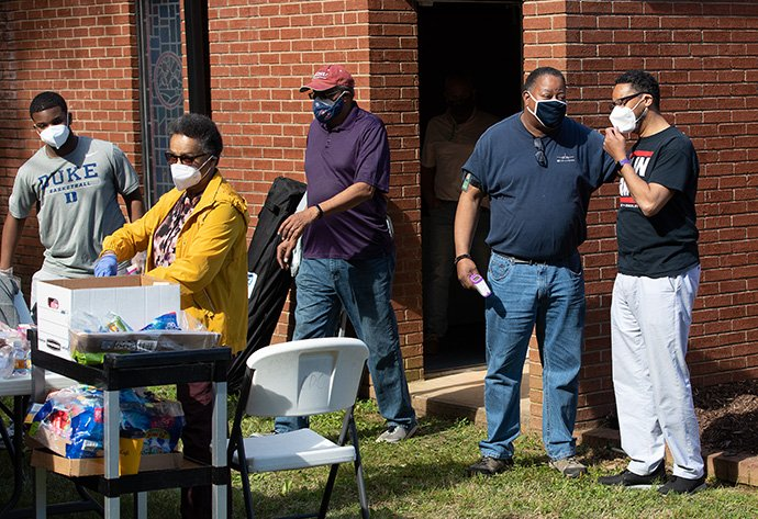 The Rev. Otto Harris (right) visits with church volunteer Andra Sutton outside St. Mark's United Methodist Church in Charlotte, N.C., which was holding a COVID-19 vaccination clinic, while other volunteers prepared snack bags for vaccine recipients as they exited the church. From left are: Walter Hand III, Patricia Moore and André Dingle. Photo by Mike DuBose, UM News.