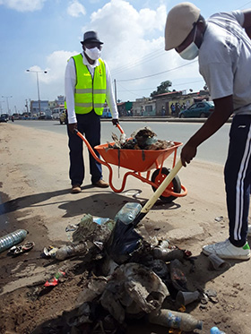 The Rev. Bernardo Neto (left) and Mauro de Oliveira clean garbage from a street in Cazenga, Angola. Neto is superintendent of The United Methodist Church's Luanda District. Photo by Augusto Bento, UM News.