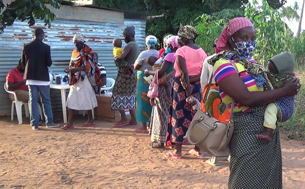 Durante as consultas em Mabumbuza, Moçambique, mães com seus filhos menores passam da esquina farmacêutica para receberem medicamentos. Foto de António Wilson.