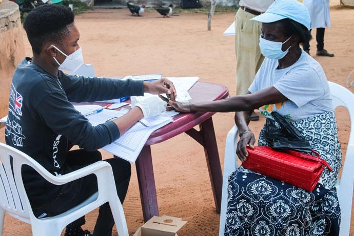 Técnico Joaquim Luís realizando teste de malária em uma paciente em Mabumbuza, Moçambique, durante a brigada móvel. Foto de António Wilson.