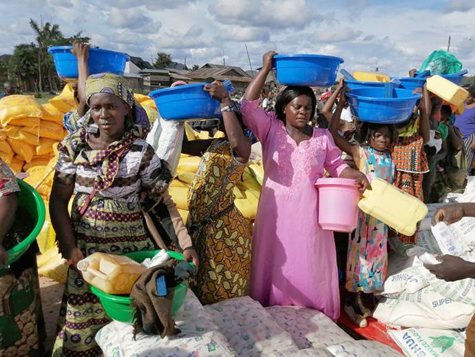 Des femmes déplacées transportent de la nourriture et d'autres fournitures qu'elles ont reçues d'UMCOR à Beni, RDC. Plus de 850 ménages vulnérables ont bénéficié de cette aide. Photo de Philippe Kituka Lolonga, UM News.