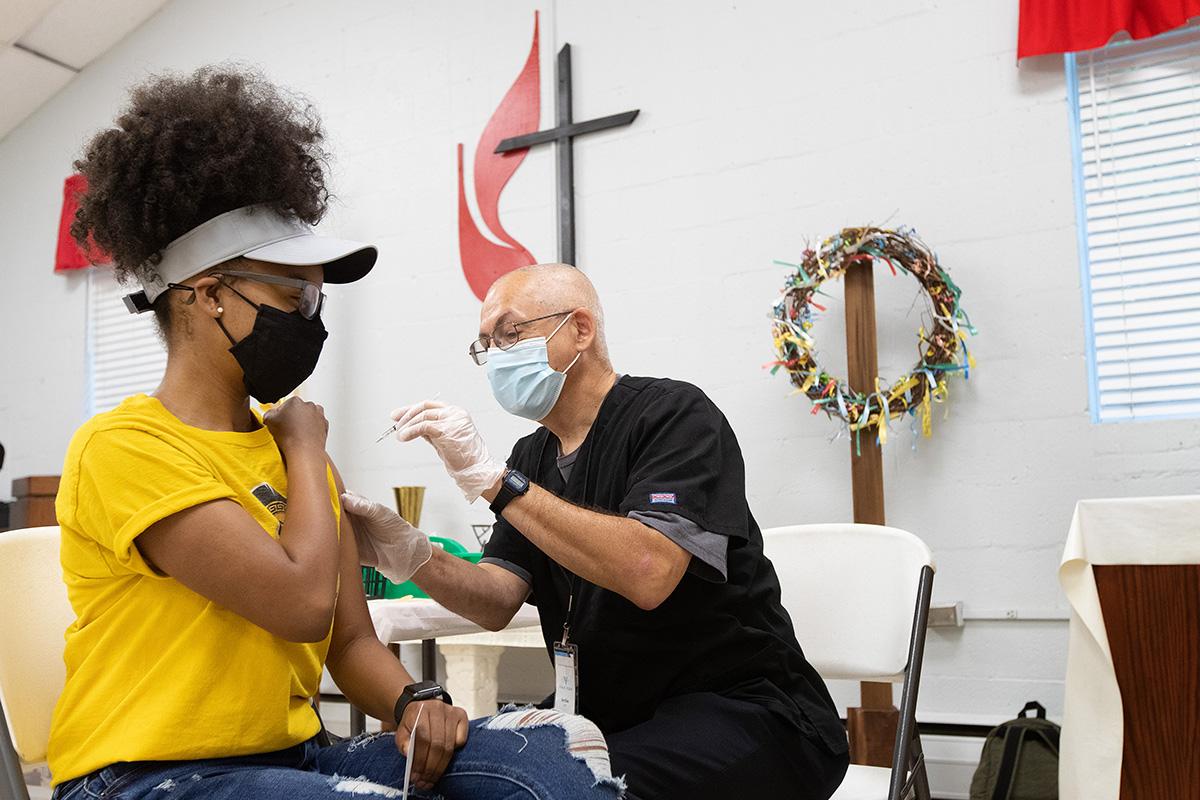 Ashlee Hand recibe una vacuna COVID-19 de EMT Archie Coble durante una clínica en la Iglesia Metodista Unida (IMU) San Marcos en Charlotte, Carolina del Norte, en abril. Los/as expertos/as en salud dicen que muchas personas confían en sus líderes religiosos/as para abordar sus preocupaciones sobre la vacunación COVID-19.