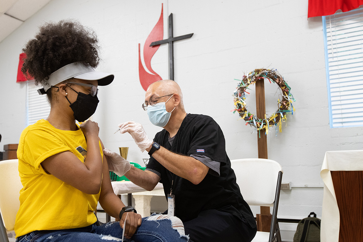 Ashlee Hand receives a COVID-19 vaccination from EMT Archie Coble during a clinic at St. Mark's United Methodist Church in Charlotte, N.C., in April. Health experts say many people trust their faith leaders to address their concerns about getting a COVID-19 vaccination.