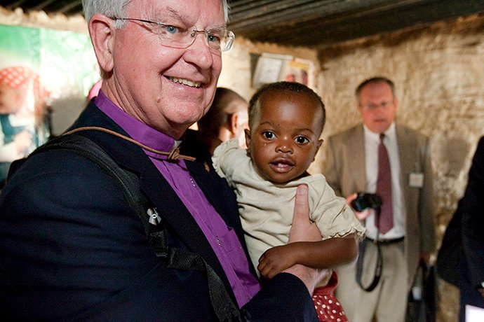 James E. Dorff, former bishop, holds 18-month-old Dunongo after her family received a mosquito net bought with funds from The United Methodist Church at their home in Lubumbashi, Congo in 2010. File photo by Mike DuBose, UM News.