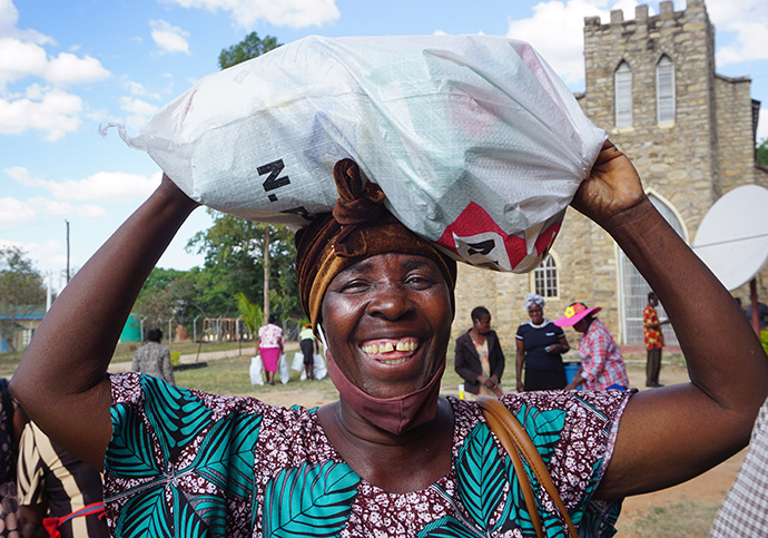 Monica Maposa carries a bundle of donated food and sanitation supplies she received during a distribution at Murewa Center United Methodist Church outside Harare, Zimbabwe. Photo by Kudzai Chingwe, UM News.