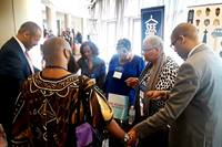 The Rev. Jacqui King (second from right) clasps hands and prays with people at the Discipleship Ministries booth during the 2019 meeting of Black Methodists for Church Renewal in Atlanta. Photo courtesy of King.