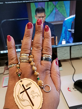 King prays with United Methodist-made prayer beads as she watches a 2019 special General Conference session online. Photo courtesy of King.