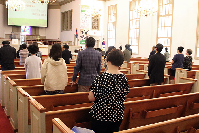 Members of Emmaus United Methodist Church worship together while following COVID-19 safety protocols in May. Members of the congregation wore face masks and practiced social distancing while a transparent screen stood in front of the altar. Photo by the Rev. Thomas Kim, UM News.