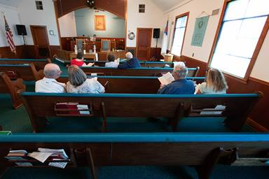 A congregation of seven sings during worship at Oakton United Methodist Church outside Clinton, Ky. Pastor Laura Vincent plays the piano behind the altar. Small, rural churches struggled through the coronavirus pandemic, but many of them are now enjoying the return to in-person services and looking to the future.