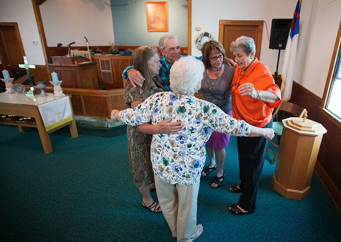 Church members share a group hug with pastor Laura Vincent (second from right) following worship at Oakton United Methodist Church near Clinton, Ky., in 2015. Prior to the COVID-19 pandemic the small congregation shared a hug with their pastor each week and are looking forward to being able to revive the tradition. File photo by Mike DuBose, UM News.