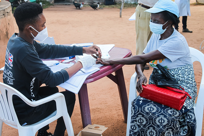 Joaquim Luís performs a malaria test on a patient during a mobile clinic brigade set up in Mabumbuza, Mozambique. The clinics, an outreach project of The United Methodist Church in Mozambique, serve isolated communities. Photo by António Wilson, UM News.