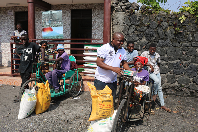 Rebeca Lamirwa, seated on her hand-cranked tricycle, receives relief supplies reserved for people with handicapping conditions from the United Methodist Committee on Relief and Connexio Switzerland in Goma, Congo. Photo by Philippe Kituka Lolonga, UM News.