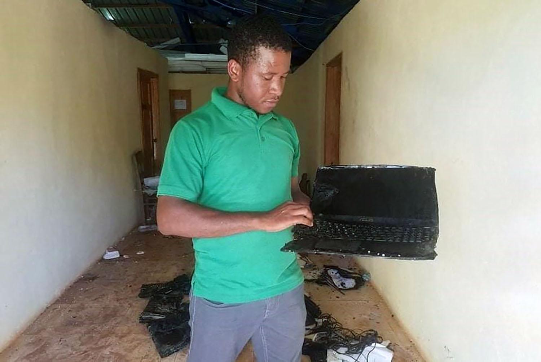 Mario Damis, coordinador de HAPITech, el centro de capacitación vocacional de Haitian Assets for Peace International, inspecciona una pila de 15 computadoras portátiles destruidas después de que el almacén se quemó en la madrugada del 6 de julio. Ahora su prioridad es restaurar el Internet de HAPI para ayudar a restablecer las comunicaciones tan necesarias, en este tiempo turbulento que vive Haití. Foto cortesía de Valerie Mossman-Celestin